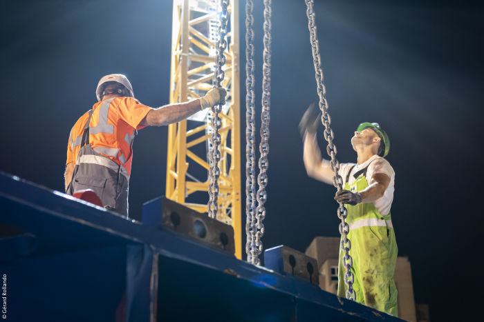 Photo d'ouvriers au travail après l'acheminement d'un convoi exceptionnel sur un chantier du Grand Paris Express