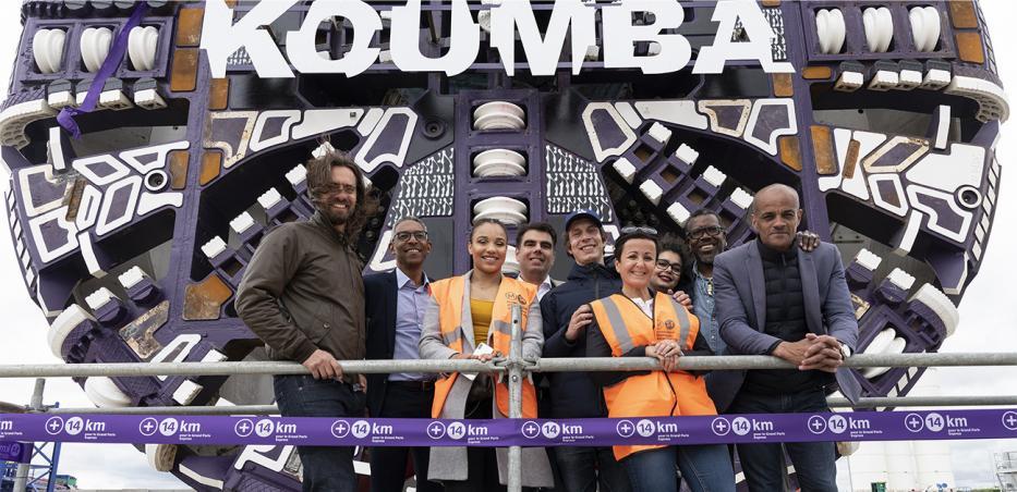 Photo de Koumba Larroque entourée de l'équipe ayant réalisé un travail artistique sur la roue de coupe du tunnelier et de l'équipe projet le jour du baptême.