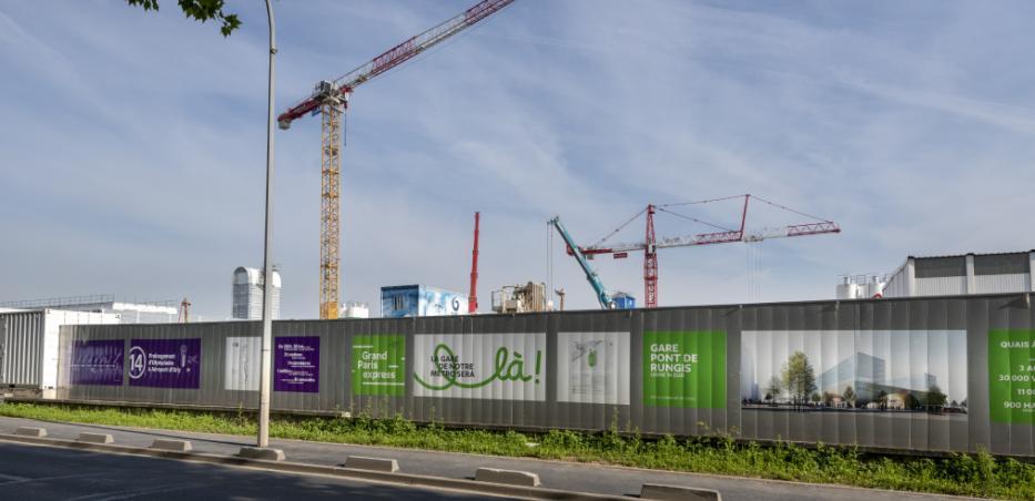 Photo de l'extérieur du chantier de la future gare Pont de Rungis à Thiais, avec une vue sur les palissades habillées avec la communication du projet