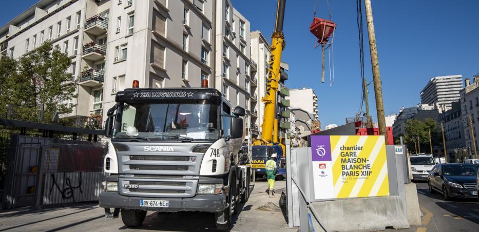 Photo de la sortie d'un camion du chantier de la future gare Maison-Blanche Paris XIIIe sur l'avenue d'Italie