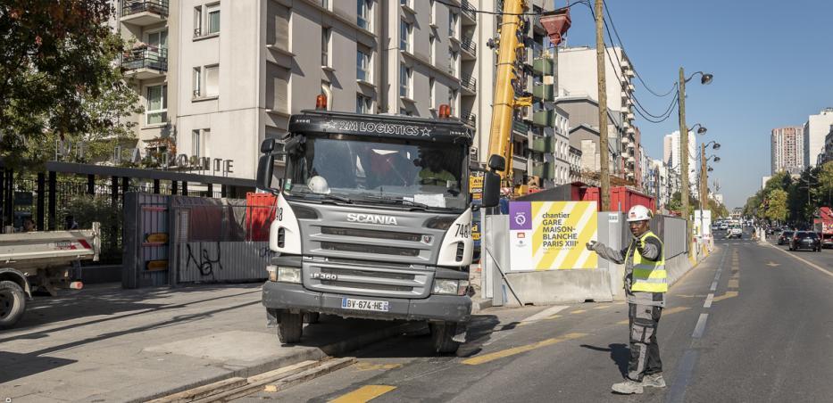 Photographie de la sortie d'un camion du chantier de la future gare Maison-Blanche Paris XIIIe sur l'avenue d'Italie.