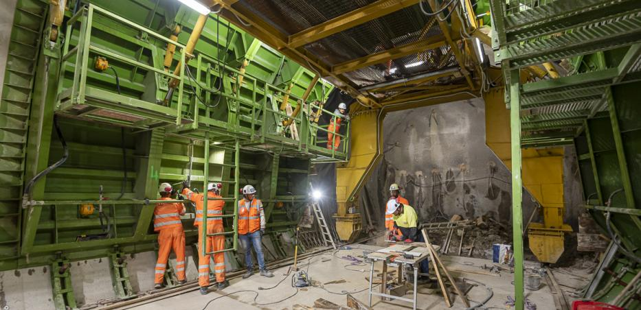 Photo des travaux de construction du tunnel de raccordement du prolongement sud à la ligne 14 existante. Un impressionnant outil de coffrage bétonne la galerie au fur et à mesure du creusement effectué au brise-roche.