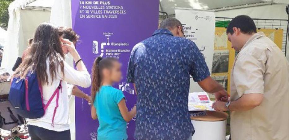 Photo d'un échange entre des Chevillais et le chargé d'information de proximité de la ligne 14 Sud sur le stand info projet +14 à la fête communale de Chevilly-Larue