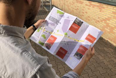 Photographie d'un homme tenant le Guide du chantier de la Petite ceinture à Maison-Blanche.