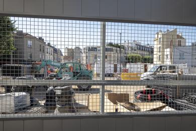 Photo du chantier vu depuis l'extérieur à travers une fenêtre grillagée