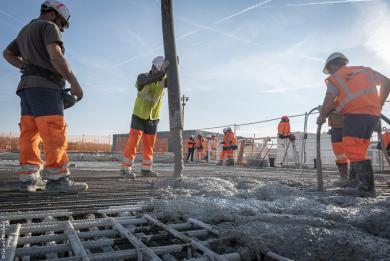 Photo d'ouvriers injectant du béton autour des armatures métalliques sur un chantier de la ligne 14 Sud