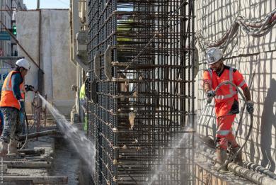 Photo d'ouvriers qui érigent la cage d'armature d'une paroi moulée sur un chantier du Grand Paris Express